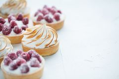 Delicious lemon and raspberry tartlets with meringue on a white vintage plate. Sweet treat on a light blue background. copy space.  Royalty Free Stock Photography