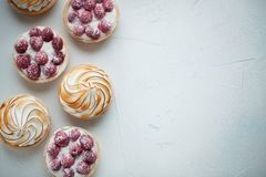 Delicious lemon and raspberry tartlets with meringue on a white vintage plate. Sweet treat on a light blue background. Flat lay an. D copy space. Top view Royalty Free Stock Photo