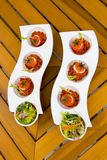 Delicious light appetizers. A view of light snacks or appetizers with green salad and small tomatoes filled with creme cheese displayed in two decorative serving Royalty Free Stock Photo