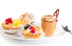 Delicious little fruit cakes near cake with chocolate and coffee Royalty Free Stock Images