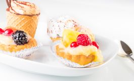 Delicious little fruit cakes near cake with chocolate Royalty Free Stock Image