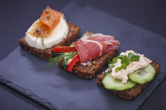 Delicious little sandwiches with tuna, cheese, prosciutto and ve Royalty Free Stock Photos
