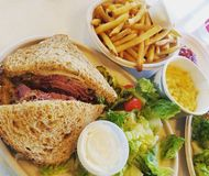 Delicious lunch. Pastrami and french fries with a salad and mac and cheese Royalty Free Stock Photo