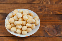 Delicious macadamia nuts on  plate on  wooden background Royalty Free Stock Photo