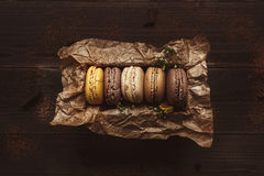 Delicious macaroons in gift box on the wooden table, top view Royalty Free Stock Images