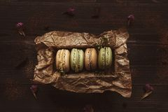 Delicious macaroons in gift box on the wooden table, top view.  Stock Photo