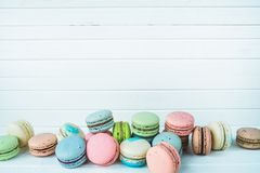 Delicious macaroons or macaron on a white wooden background, almond cookies on a table, copy space. Delicious macaroons or macaron on a white wooden background Stock Photo