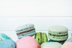 Delicious macaroons or macaron on a white wooden background close-up, copy space. Delicious macaroons or macaron on a white wooden background close-up, copy Royalty Free Stock Photography