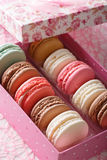 Delicious macaroons in a pink gift box macro on a table. vertica Royalty Free Stock Images