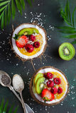 Delicious mango  smoothie topped with fresh fruits and berries a. Nd served in  coconut. Healthy vegan raw food. Top view Stock Photos