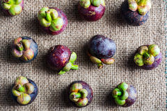 Delicious mangosteen fruit arranged on a hemp sack background, M Stock Image