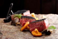 Delicious medium beef steaks with mushrooms Stock Images