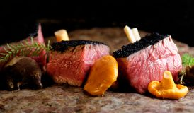 Delicious medium beef steaks with mushrooms Royalty Free Stock Image