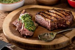 Argentine Style Steak with Chimichurri Sauce. A delicious medium rare fire grilled argentina style steak with chimichurri verde sauce Royalty Free Stock Image