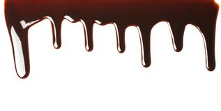 Delicious melted chocolate flowing. On white background Royalty Free Stock Photos