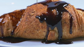 Delicious melted chocolate syrup pouring over a croissant in slow motion stock video footage