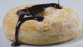 Delicious melted chocolate syrup pouring over a donut in slow motion stock footage
