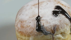 Delicious melted chocolate syrup pouring over a donut in slow motion stock video footage