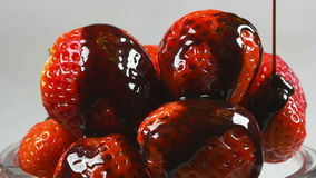 Delicious melted chocolate syrup pouring over strawberries in reverse stock video footage