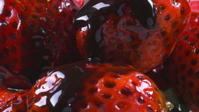 Delicious melted chocolate syrup pouring over strawberries stock video