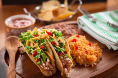 Delicious mexican food tacos served with spanish rice and refried beans with salsa Royalty Free Stock Photos