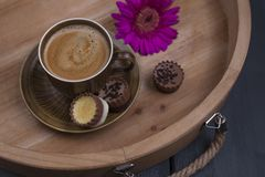 Delicious milk chocolate, a bouquet of fresh flowers and a morning aromatic coffee. Black wooden background, free space for text. royalty free stock photo