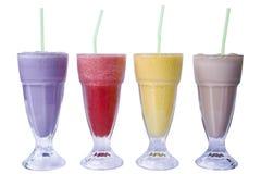 Delicious Milkshakes. Four colourful milkshakes isolated on a white background. Blueberry, Raspberry, Mango and Chocolate flavours Stock Image