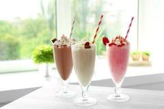 Delicious milkshakes on table. In kitchen stock photo