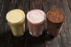 Delicious Milkshakes on Wooden Background. Top View Tasty Milkshakes on Rustic Wooden Background stock images