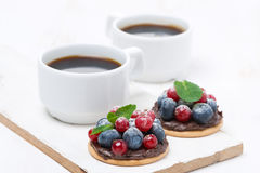 Delicious mini cakes with chocolate cream and berries Royalty Free Stock Photos