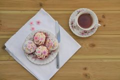 Delicious mini cakes with iced pink flower decorations for afternoon tea royalty free stock images