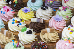 Delicious mini cupcakes. A selection of delicious mini cupcakes topped with colourful icing Stock Photo