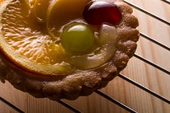 Delicious mini tarts with pudding filling and some fruits. The tart is lying on the metal support stock images