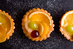 Delicious mini tarts with pudding filling and some fruits. The tarts are isolated on the black background royalty free stock images