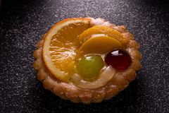Delicious mini tarts with pudding filling and some fruits. The tart is isolated on the black background stock images