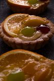 Delicious mini tarts with pudding filling and some fruits. The tarts are on the black background stock photography
