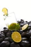 Delicious mint and lime fruit, black stones. Royalty Free Stock Images
