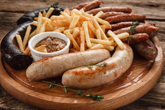 Delicious mix of grilled sausages on wood platter. Appetizing grilled sausages and french fries served with delicious sauce, close up view. Restaurant menu photo Royalty Free Stock Images