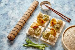 Delicious mixed kinds of chinese dumplings served on wooden stands stock photo