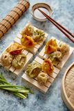 Delicious mixed kinds of chinese dumplings served on wooden stands royalty free stock photo