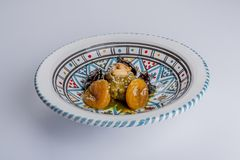 Delicious moroccan sweet dessert with prunes and dried apricots. On a white ceramic plate decorated with blue, red, green and black colors, a delicious stock photography