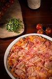 Delicious mozzarella cheese and ham pizza. Delicious pizza with mozzarella cheese, arugula, ham, bacon, tomatoes on wooden paddle next to a bottle of wine stock image