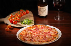 Delicious mozzarella cheese and ham pizza. Delicious pizza with mozzarella cheese, arugula, ham, bacon, tomatoes on wooden paddle next to a bottle of wine stock photos