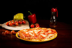 Delicious mozzarella cheese and pepper pizza. Delicious pizza with mozzarella cheese, pepper slices and red tomatoes on wooden texture royalty free stock photography