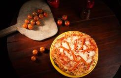 Delicious mozzarella cheese pizza. Delicious pizza with mozzarella cheese, pepper slices and red tomatoes on wooden texture stock images