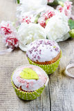 Delicious muffins with icing on wooden table Royalty Free Stock Photography
