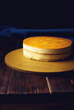 Delicious multi-layered fruit mango cake stands on circular base. Delicious multi-layered fruit mango cake stands on a circular base on a wooden table and dark Stock Photography