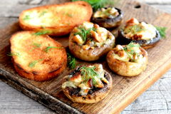 Delicious mushroom caps stuffed with cheese and meat and baked in the oven. Fried toasts of white bread. Wooden background Stock Photos