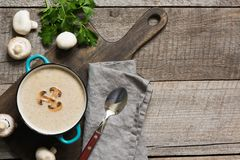 Delicious mushroom champignon soup on wooden board. View from above. Space for text. Delicious mushroom champignon soup on wooden board. Horizontal mockup, view stock photo