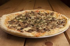 Delicious mushroom pizza on a wooden table stock photo